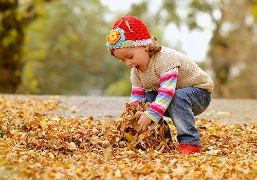 Bimba gioca con foglie d'autunno